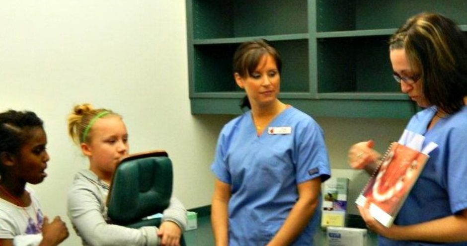 Dental assistants talking about importance of dental heath to kids